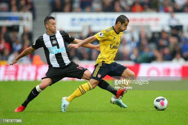 Javier Manquillo of Newcastle United tackles Henrikh Mkhitaryan of Arsenal during the Premier League match between Newcastle United and Arsenal FC at...