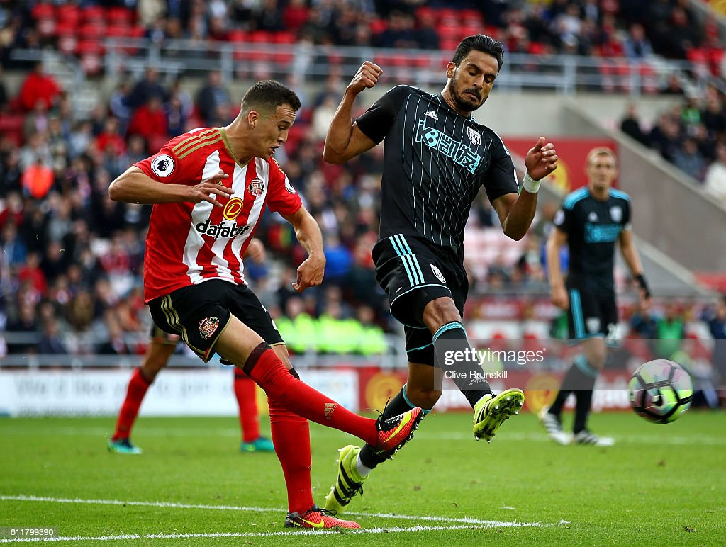 Javier Manquillo of Sunderland (L) clears the ball while under pressure from Nacer Chadli of West Bromwich Albion (R) during the Premier League match between Sunderland and West Bromwich Albion at Stadium of Light on October 1, 2016 in Sunderland, England.