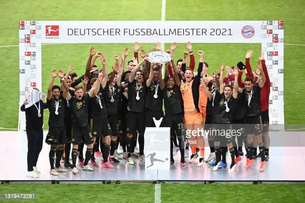 Javier Martinez, David Alaba and Jerome Boateng of FC Bayern Muenchen lift the Bundesliga Meisterschale Trophy following the Bundesliga match between...