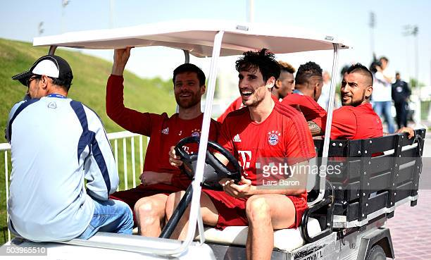 Javier Martinez drives a golf cart with teammates Xabi Alonso and Arturo Vidal during a training session at day three of the Bayern Muenchen training...