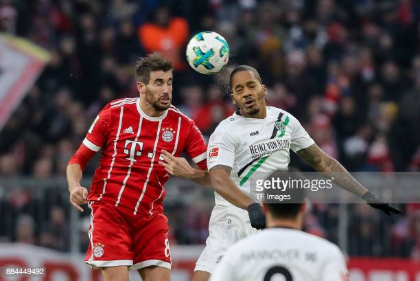 Javier Martinez of Bayern Muenchen and Charlison Benschop of Hannover battle for the ball during the Bundesliga match between FC Bayern Muenchen and...