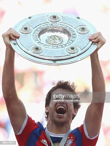Javier Martinez of Bayern Muenchen lifts the Bundesliga championship trophy in celebration after the Bundesliga match between Bayern Muenchen and VfB...