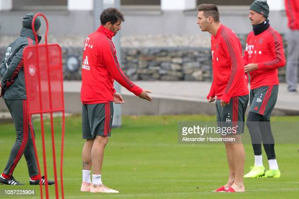 Javier Martinez of Bayern Muenchen talks to his team mate Niklas Suele of Bayern Muenchen as he arrives for a Bayern Muenchen training session at...