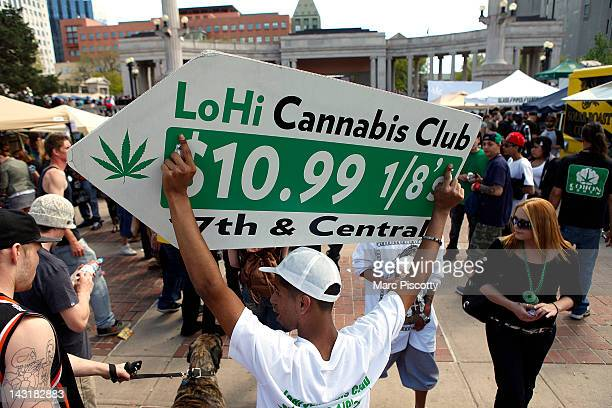 Javier Martinez uses a sign to advertise for LoHi Cannabis Club dispensary as an estimated 10000 people were expected to gather for a 4/20 marijuana...