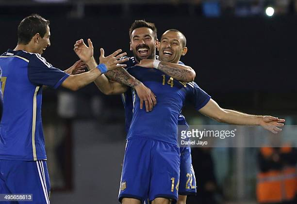Javier Mascherano celebrates Argentina's second goal with teammates Angel Di Maria and Ezequiel Lavezzi after scoring during a FIFA friendly match...