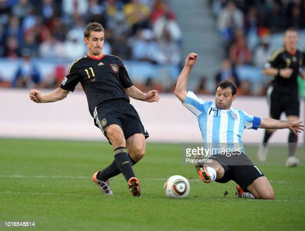 Javier Mascherano of Argentina and Miroslav Klose of Germany in action during the 2010 FIFA World Cup Quarter Final match between Argentina and...