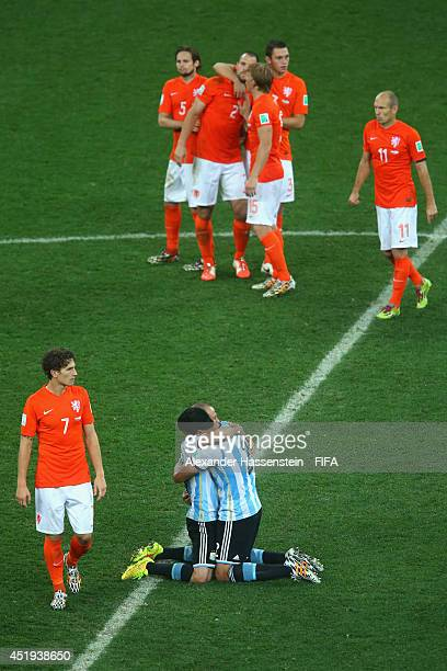 Javier Mascherano of Argentina celebrates with his team mate Ezequiel Garay defeating the Netherlands in a shootout whilst Daryl Janmaat of...