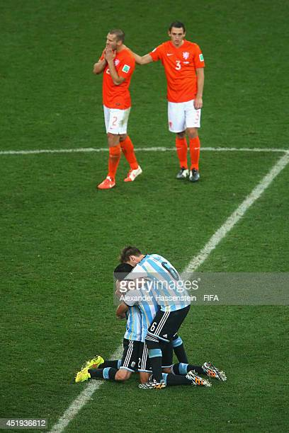 Javier Mascherano of Argentina celebrates with his team mates Ezequiel Garay and Lucas Biglia defeating the Netherlands in a shootout whilst Ron...