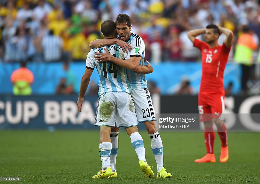 Javier Mascherano of Argentina (L) celebrates with Jose Maria Basanta of Argentina as Blerim Dzemaili of Switzerland (R) looks on after the 2014 FIFA World Cup Brazil Round of 16 match between Argentina and Switzerland at Arena de Sao Paulo on July 1, 2014 in Sao Paulo, Brazil.