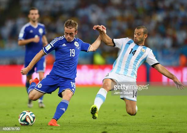Javier Mascherano of Argentina challenges Edin Visca of Bosnia and Herzegovina during the 2014 FIFA World Cup Brazil Group F match between Argentina...