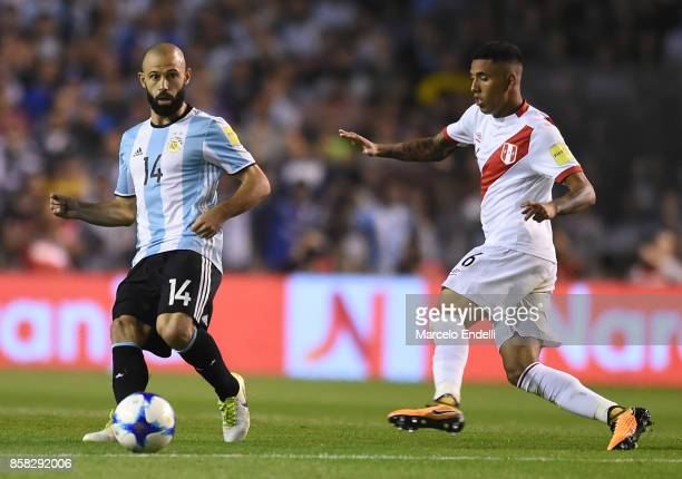 Javier Mascherano of Argentina kicks the ball followed by Miguel Trauco of Peru during a match between Argentina and Peru as part of FIFA 2018 World...