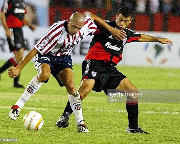 Javier Mascherano of Argentine River Plate and Omar Perez of Junior from Colombia fight for the ball during their football match in their Copa...
