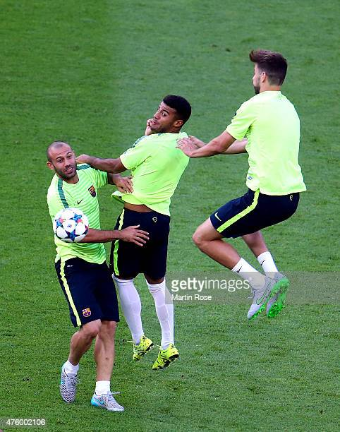 Javier Mascherano of Barcelona challenges for the ball with Rafinha and Gerard Pique during an FC Barcelona training session on the eve of the UEFA...