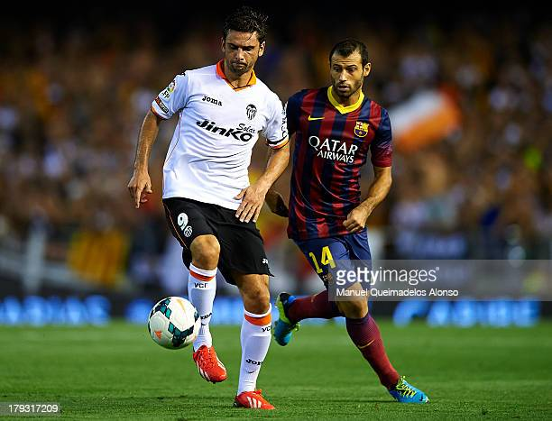 Javier Mascherano of Barcelona competes for the ball with Helder Postiga of Valencia during the La Liga match between Valencia CF and FC Barcelona at...
