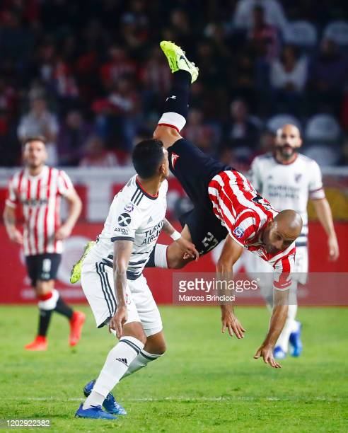 Javier Mascherano of Estudiantes falls after clashing with Matias Suarez of River Plate during a match between Estudiantes and River Plate as part of...