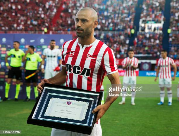 Javier Mascherano of Estudiantes poses with a plaque given to him by San Lorenzo soccer club to honor his career before a match between San Lorenzo...