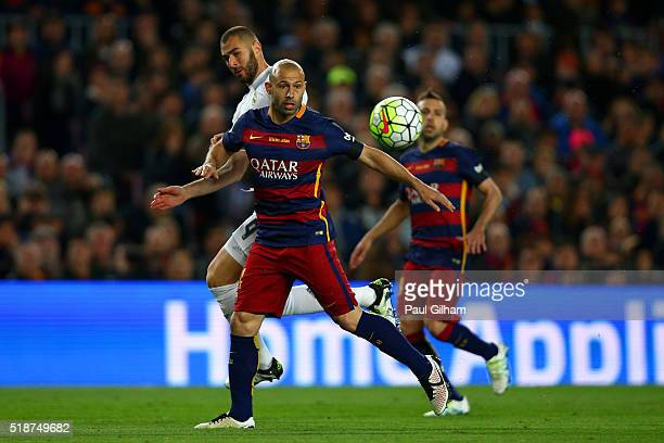 Javier Mascherano of FC Barcelona battles for the ball with Karim Benzema of Real Madrid CF during the La Liga match between FC Barcelona and Real...