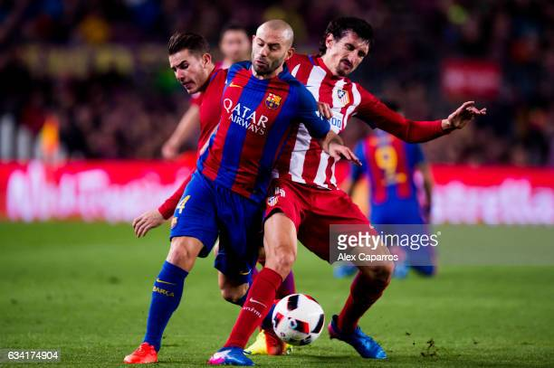 Javier Mascherano of FC Barcelona fights for the ball with Lucas Hernandez and Stefan Savic of Atletico de Madrid during the Copa del Rey semifinal...