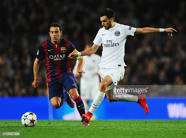 Javier Pastore is watched by Xavi of Barcelona during the UEFA Champions League Quarter Final second leg match between FC Barcelona and Paris...