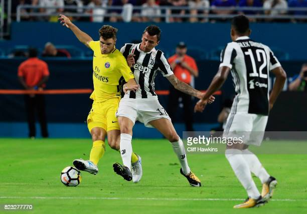 Javier Pastore of Paris SaintGermain and Mario Mandzukic of Juventus vie for possession in the first half during their International Champions Cup...