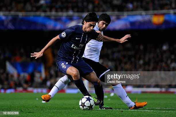 Javier Pastore of Paris SaintGermain duels for the ball with Ever Banega of Valencia CF during the UEFA Champions League Round of 16 first leg match...