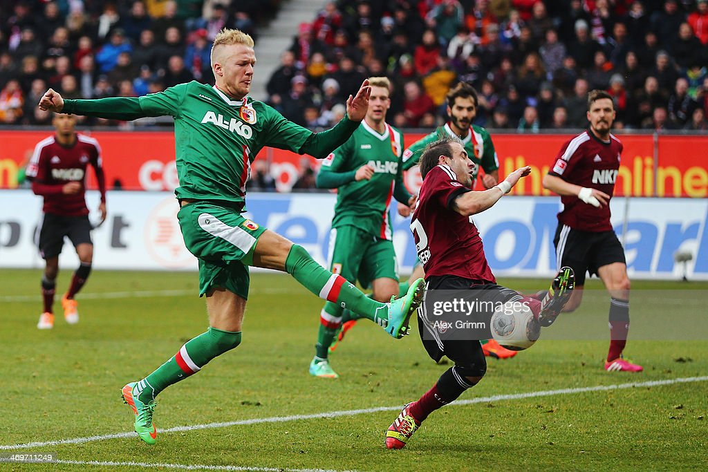 Javier Pinola (R) of Nuernberg blocks a shot by Kevin Voigt of Augsburg during the Bundesliga match between FC Augsburg and 1. FC Nuernberg at SGL Arena on February 16, 2014 in Augsburg, Germany.