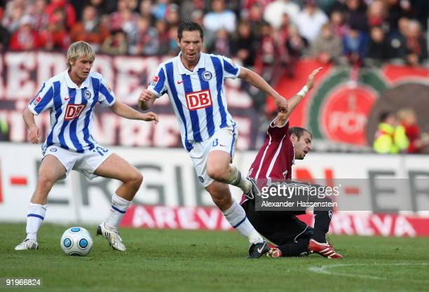 Javier Pinola of Nuremberg battles for the ball with Pal Dardai of Berlin and his team mate Marc Stein during the Bundesliga match between 1 FC...