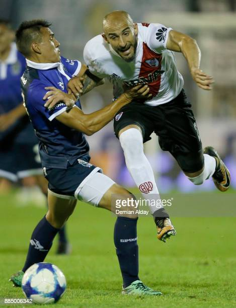 Javier Pinola of River Plate fights the ball with Gabriel Bolivar of Gimnasia y Esgrima during a match between Gimnasia y Esgrima La Plata and River...