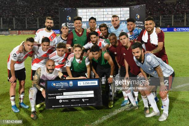 Javier Pinola of River Plate holds the cheque prize with teammates as they celebrate victory after a Semi Final match between River Plate and Club...
