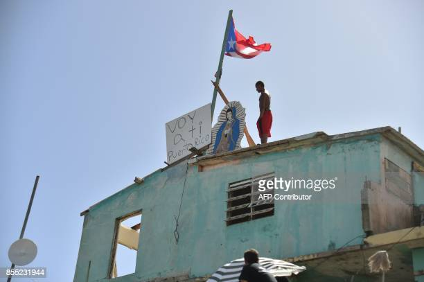 Javier places on his house next to a flag of Puerto Rico a placard that read in spanish 'Voy a ti Puerto Rico' in Yabucoa in the east of Puerto Rico...