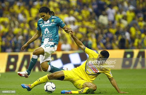Javier Rodriguez of America vies for the ball with Carlos Pena of Leon during their 2013 Mexican Apertura tournament football final match in Mexico...