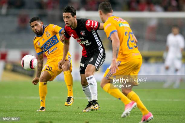 Javier Salas of Atlas fights for the ball with Javier Aquino of Tigres during the 8th round match between Atlas and Tigres UANL as part of the Torneo...