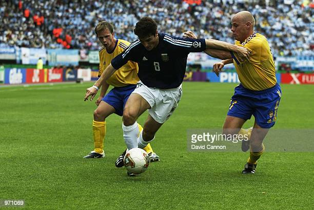 Javier Zanetti of Argentina holds off Magnus Svensson of Sweden during the Argentina v Sweden Group F World Cup Group Stage match played at the...