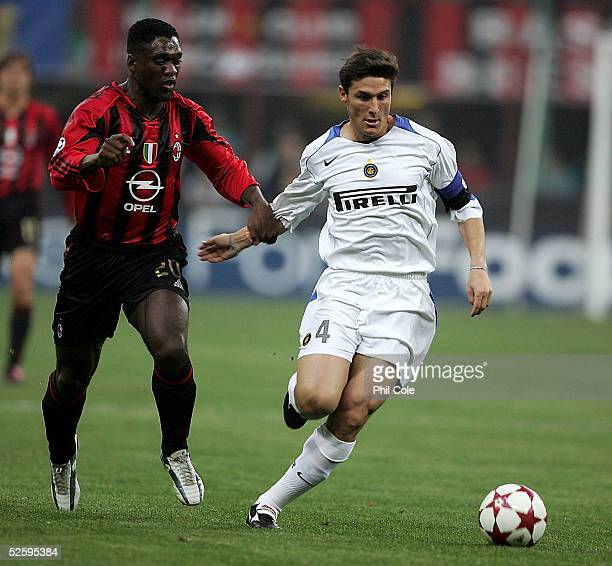 Javier Zanetti of Inter is challenged by Clarence Seedorf of AC during the Champions League Quarter Final First leg match between AC Milan and Inter...