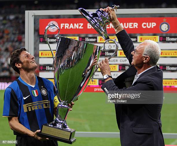 Javier Zanetti of Milan receives the trophy from Franz Beckenbauer after beating Bayern with 01 in the Beckenbauer Cup match between FC Bayern...