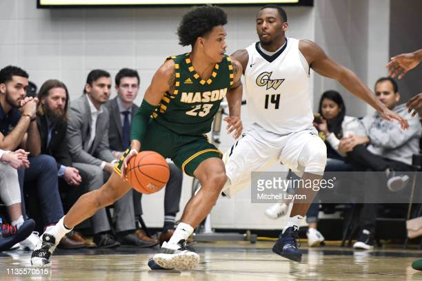 Javon Greene of the George Mason Patriots dribbles by Maceo jack of the George Washington Colonials during a college basketball game at the Smith...
