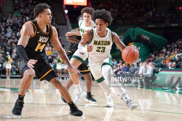 Javon Greene of the George Mason Patriots dribbles by Marcus SantosSilva of the Virginia Commonwealth Rams during a college basketball game against...