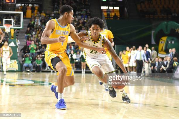 Javon Greene of the George Mason Patriots dribbles the ball around LaQuentin Collins of the Southern University Jaguars during a college basketball...