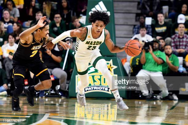 Javon Greene of the George Mason Patriots dribbles the ball by Marcus Evans of the Virginia Commonwealth Rams during a college basketball game at the...