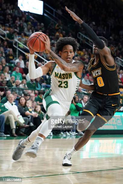 Javon Greene of the George Mason Patriots drives to basket by De'Riante Jenkins of the Virginia Commonwealth Rams during a college basketball game at...