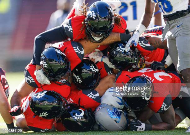 Javon Ivory of the Memphis Tigers is tackled by seven members of the Cincinnati Bearcats defense during the first half at Nippert Stadium on October...