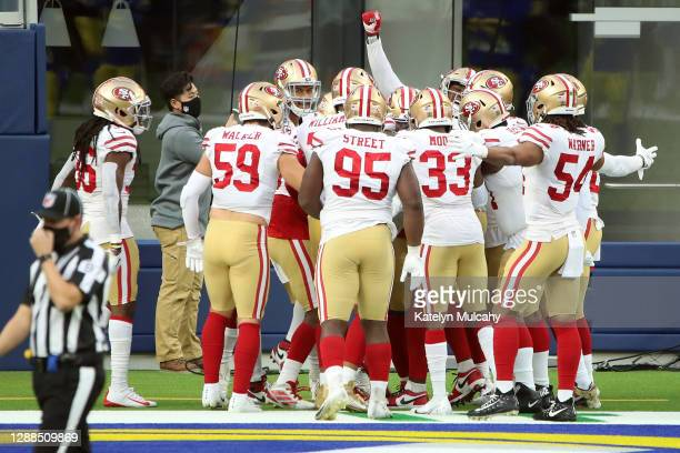 Javon Kinlaw of the San Francisco 49ers celebrates with teammates after returning an interception for a touchdown during the third quarter against...