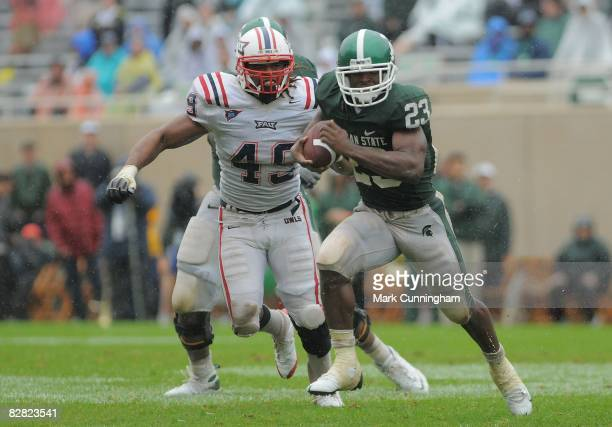 Javon Ringer of the Michigan State Spartans carries the ball past Andre Clark of the Florida Atlantic University Owls on September 13, 2008 at...