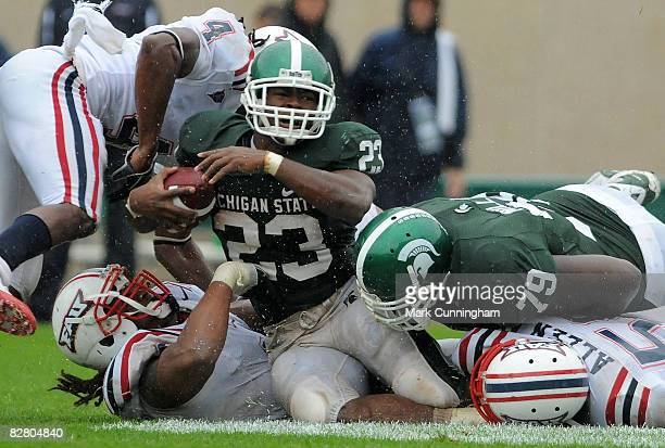 Javon Ringer of the Michigan State Spartans is tackled by the Florida Atlantic University Owls on September 13, 2008 at Spartan Stadium in East...