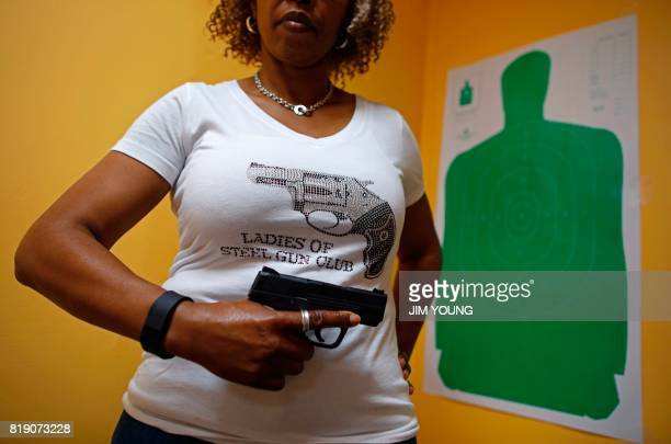 Javondlynn Dunagan of JMD Defense and Investigations holds her Smith and Wesson MP Shield 9mm gun in her training classroom in Chicago Illinois on...