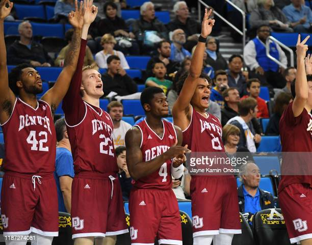 JaVonni Bickham, Tristan Green, Taelyr Gatlin and Robert Jones of the Denver Pioneers celebrate on the bench after a 3 point basket in the second...