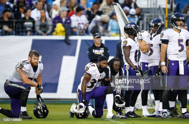 Javorius Allen and Marshal Yanda of the Baltimore Ravens take a knee during fourth quarter of a game against the Tennessee Titans after a player was...
