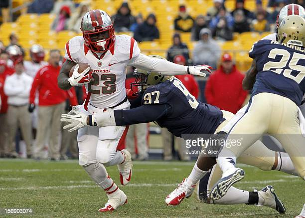 Jawan Jamison of the Rutgers Scarlet Knights is tackled in the back field by Aaron Donald of the Pittsburgh Panthers during the game on November 24...