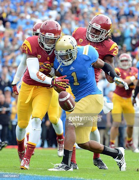 Jawanza Starling and Josh Shaw of the USC Trojans break up a pass to Shaquelle Evans of the UCLA Bruins during the first half at Rose Bowl on...