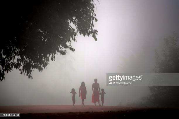 Jawaruwa Waiapi and his family walk amidst fog, early in the morning, at the Manilha village in the Waiapi indigenous reserve in Amapa state in...